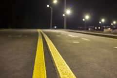 Wide modern smooth empty illuminated with street lamps asphalt highway with bright white marking sign line at night. Speed, safety. Comfortable journey and stock photo
