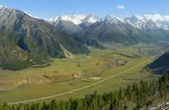 Wide mountain gorge with a river running down the river and an automobile road to Dombai with wooded mountain slopes. And snow-capped peaks. Karachay-Cherkess Stock Photo