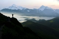Wide mountain panorama. Small silhouette of tourist with backpack on rocky mountain slope with raised hands over valley covered royalty free stock images