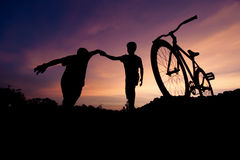 Wide moving silhouettes of two boys holding hands Stock Images