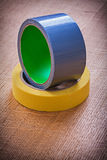 Wide and narrow duct tapes on vintage brown wood Royalty Free Stock Photo