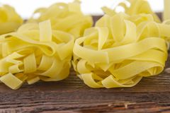 Wide noodles for cooking on a  wooden base. Wide, delicious noodles for cooking on a brown wooden base royalty free stock images