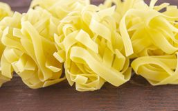 Wide noodles for cooking on a  wooden base. Wide, delicious noodles for cooking on a brown wooden base royalty free stock photos