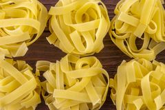 Wide noodles for cooking on a  wooden base. Wide, delicious noodles for cooking on a brown wooden base royalty free stock photography