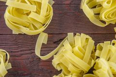 Wide noodles for cooking on a  wooden base. Wide, delicious noodles for cooking on a brown wooden base stock images