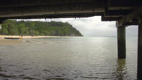Wide ocean and beach shot. A wide shot of the ocean while camera is under a bridge. Camera pans to the left to show a  beach and for then pans to the right stock footage