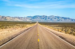 Wide open road and distant mountains in wide open Nevada desert along the Extraterrestrial Highway. Wide open road through Nevada Desert near Area 51. The royalty free stock image