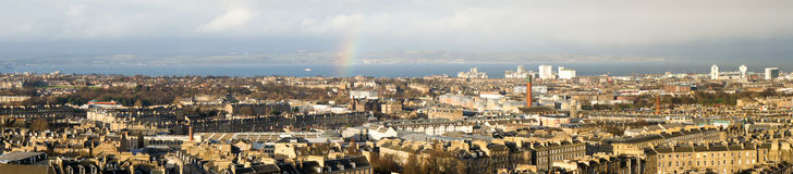 Wide panorama of Edinburgh with rainbow, in the background the water of the Firth of Forth, and beyond that the opposite shore. Stock Image