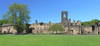 Wide panorama of Kirkstall Abbey ruins, Leeds, UK. Wide panoramic view of Kirkstall Abbey ruins, taken in birght summer sunlight, Leeds, West Yorkshire, England Royalty Free Stock Image