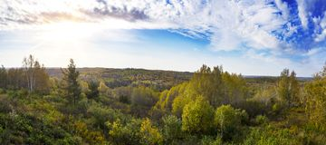 Wide panorama landscape shot of a green meadow with colorful trees and blue sky in autumn. Royalty Free Stock Photos