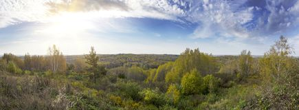 Wide panorama landscape shot of a green meadow with colorful trees and blue sky in autumn. Stock Photos