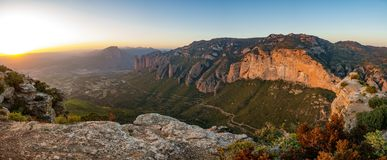 Bright view of Mallos of Riglos at sunset from top of the mountain. Wide panorama of Mallos of Riglos at dusk from top of viewpoint with bright sun Stock Image