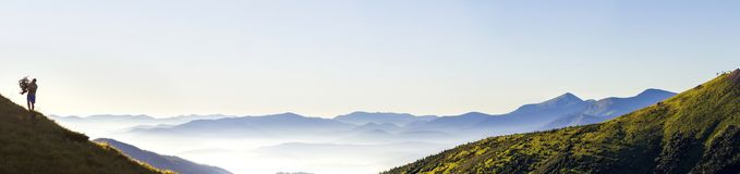 Wide panorama of morning mountain hills and lonely hiker tourist. Carpathian mountains at sunrise stock photography