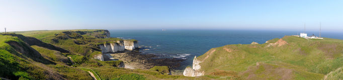 Wide panorama of sea and cliffs in Flamborough, UK. Wide panoramic view of sea and cliffs during low tide, taken in bright summer sunlight, Flamborough, east Stock Photography