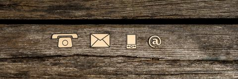 Wide panorama  top view of  contact icons. Phone, web, mobile and mail on rustic wood Royalty Free Stock Images