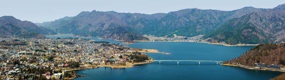 Wide panorama of the town of Fujikawaguchiko and Lake Kawaguchi at the foothills of Mount Fuji in Japan. Panoramic view of Lake Kawaguchi in Japan and the stock photography