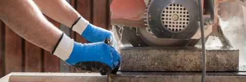 Wide panorama view of a building contractor using a circular saw Royalty Free Stock Photography