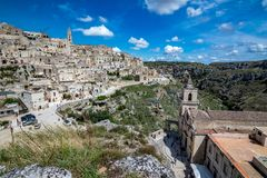 Wide panoramic cityscape view of Matera, Italy. MATERA, ITALY - AUGUST 27, 2018: High angle summer day panoramic view over Church of Saint Peter or Chiesa di San stock photo
