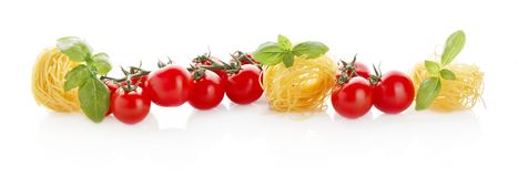 Wide panoramic long horizontal view of tomatoes,pasta and basil on white Stock Image