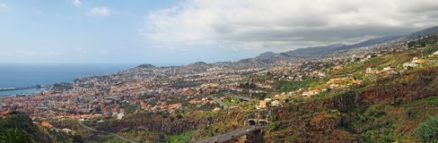 Wide panoramic view of funchal in madeira showing the city surrounded by hills and mountains with forests and motorway bridge in. A 180 degree wide panoramic stock photos