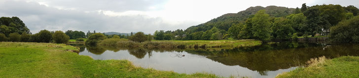 Wide Panoramic view of pond in Ambleside countryside, Cumbria, U. Wide Panoramic view of pond and beautiful reflections in Ambleside countryside, Cumbria, UK Stock Photography