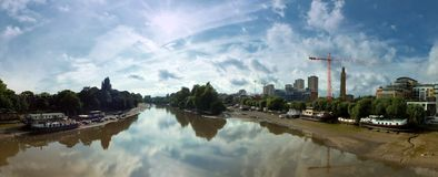 Wide panoramic view of the thames at kew brige with houseboats and surrounding buildings. With dramatic clouds stock photo