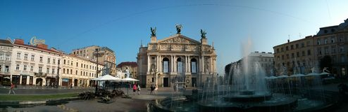 Wide panorana of Lviv theatre building streets and fountain. Wide panorama of Lviv theatre building streets and fountain Royalty Free Stock Images