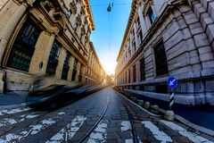 A wide passage between the old massive building with a pedestrian crossing in Milan, Italy. Toning Stock Image