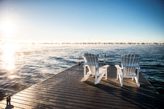 Wide photo of Muskoka Chairs on a dock with sun rising and mist Royalty Free Stock Images