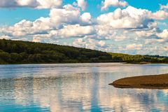 Wide quiet deep river flowing into the distance with sandy and hilly coasts covered with forest sunny with day and white clouds royalty free stock photo