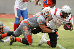 Wide Receiver being tackled. Photo demonstrating a wide receiver getting tackled during a game between the South Florida Conference and Gulf Coast Conference on Royalty Free Stock Image