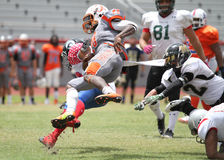 Wide Receiver being tackled. Photo demonstrating a wide receiver getting tackled during a game between the South Florida Conference and Gulf Coast Conference on Stock Images