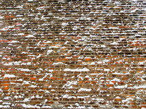 Wide red brick wall covered with snowflakes. Front view of red brick and concrete wall lightly covered with snow flakes, winter time illustration, background Royalty Free Stock Images