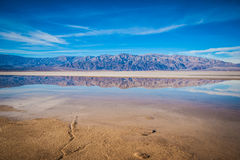 Wide Reflection of Desert Mountains. Calm water reflects the mountains and salt flat of Death Valley National Park Stock Photo