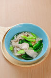 Wide rice noodles in gravy. Noodles in thick gravy with pork and flower on the table Stock Images