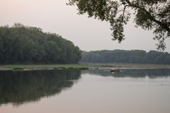 Wide river flowing across green forest. Fall. Evening. Reflections of trees in the calm water. Sundown Stock Photography