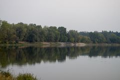 Wide river flowing across green forest. Fall. Evening. Reflections of trees in the calm water. Sundown Stock Photo