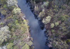 Wide river flowing through spring forest, aerial shot Stock Images