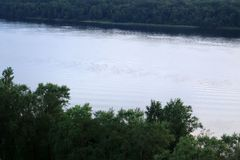 Wide river. A wide river flows along a dense forest Stock Photography