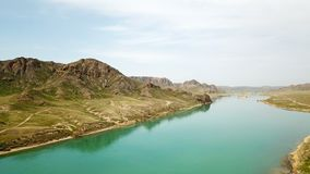 Wide river among the green canyon. Large green hills and steppe. royalty free stock image
