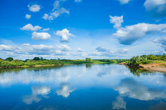 Wide river with reflection and green bush on coasts and blue clo Royalty Free Stock Photos