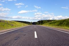 Wide road. A wide road of asphalt built through a forest with different trees, sunny weather with a blue sky stock photo