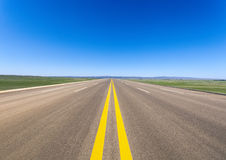 Wide road in prairie. Against a blue sky Royalty Free Stock Photography
