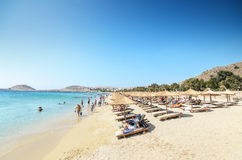 Wide sand beach with tourists, umbrellas and beds in Mykonos, Greece. Stock Images
