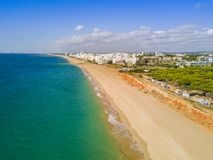 Wide sandy beach in touristic Quarteira and Vilamoura, Algarve,. Sandy beach along cliffs and RVs in touristic resorts of Quarteira and Vilamoura, Algarve Royalty Free Stock Photography