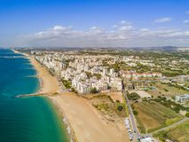 Wide sandy beach in touristic Quarteira and Vilamoura, Algarve,. Sandy beach along Recreational Vehicles and white architecture of Quarteira and Vilamoura Royalty Free Stock Photo