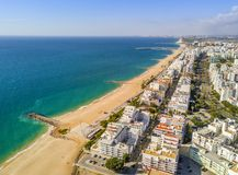 Wide sandy beach in touristic Quarteira and Vilamoura, Algarve,. Wide sandy beach in touristic resorts of Quarteira and Vilamoura, Algarve, Portugal Stock Images