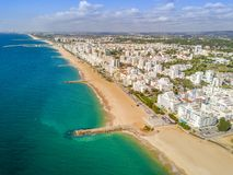 Wide sandy beach in touristic Quarteira and Vilamoura, Algarve,. Wide sandy beach in touristic resorts of Quarteira and Vilamoura, Algarve, Portugal Royalty Free Stock Photography
