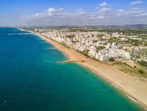 Wide sandy beach in touristic Quarteira and Vilamoura, Algarve,. Wide sandy beach in touristic resorts of Quarteira and Vilamoura, Algarve, Portugal Royalty Free Stock Photo