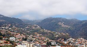 Wide scenic panoramic aerial cityscape of the city of funchal in Madeira with buildings of the city in front of mountains with stock photo